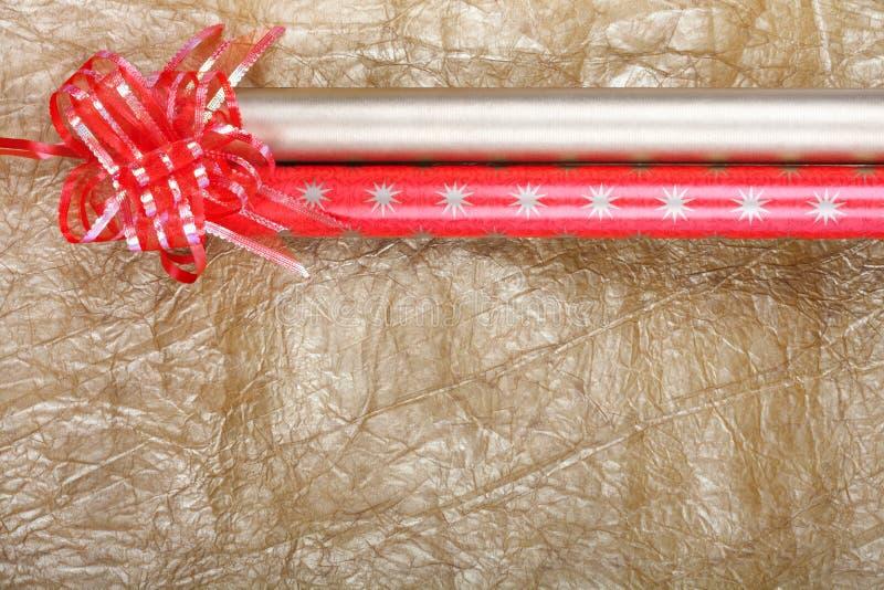 Rolls пестротканой упаковочной бумаги с красным смычком для подарков на g стоковое изображение rf