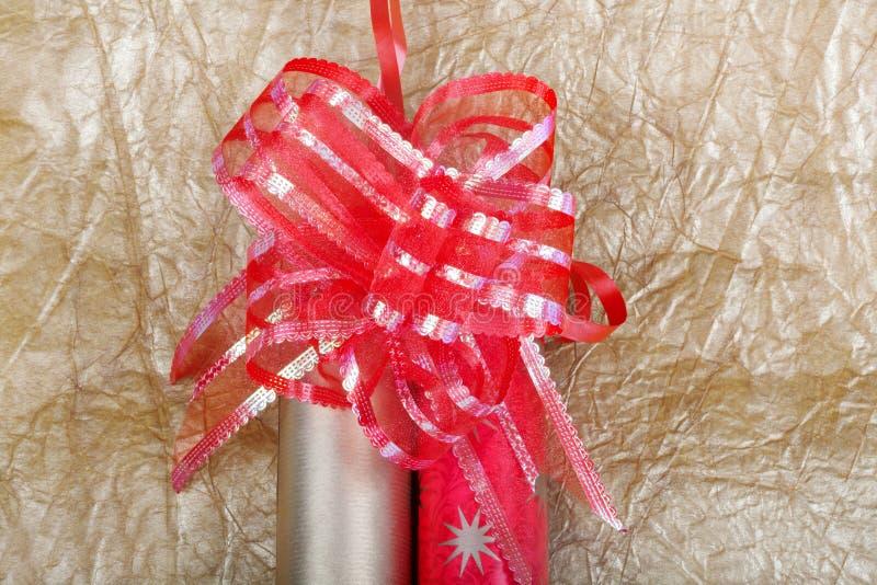 Rolls пестротканой упаковочной бумаги с красным смычком для подарков на g стоковые изображения