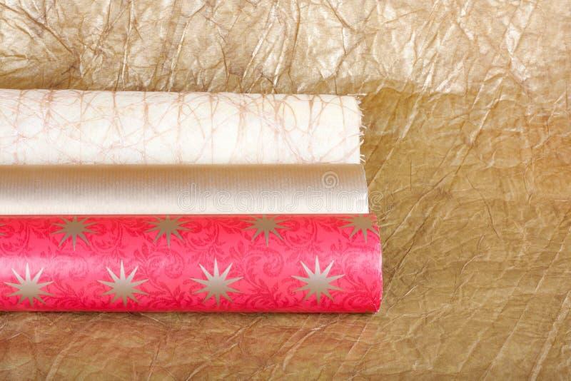 Rolls пестротканой упаковочной бумаги для подарков на backgroun золота стоковое изображение rf