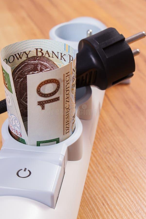 Rolls польских денег валюты в прокладке электропитания и disconnected штепсельной вилке, стоимостях энергии стоковые фотографии rf