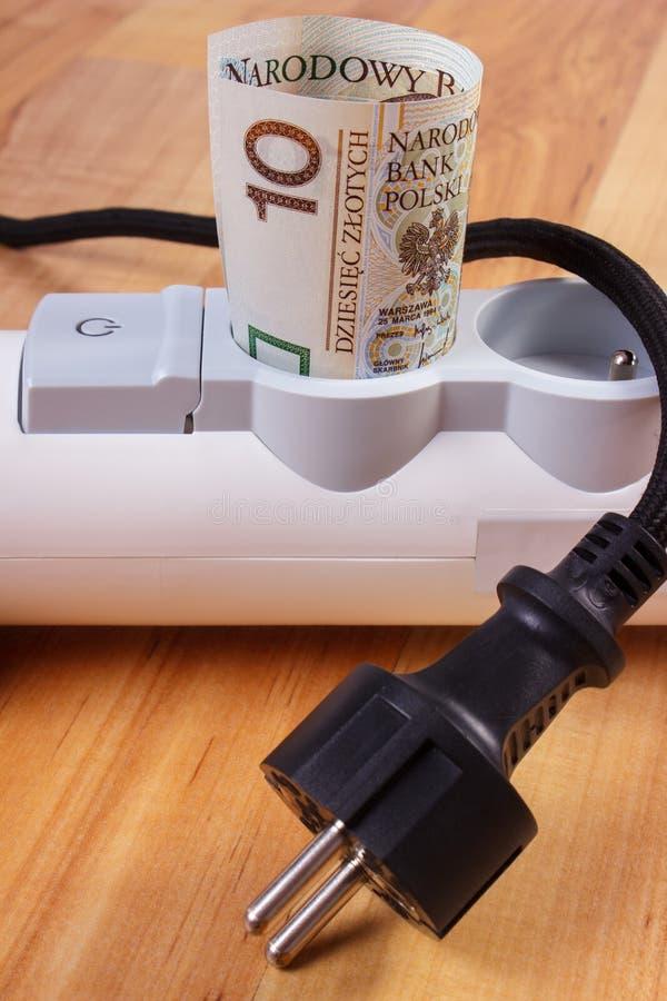 Rolls польских денег валюты в прокладке электропитания и disconnected штепсельной вилке, стоимостях энергии стоковая фотография