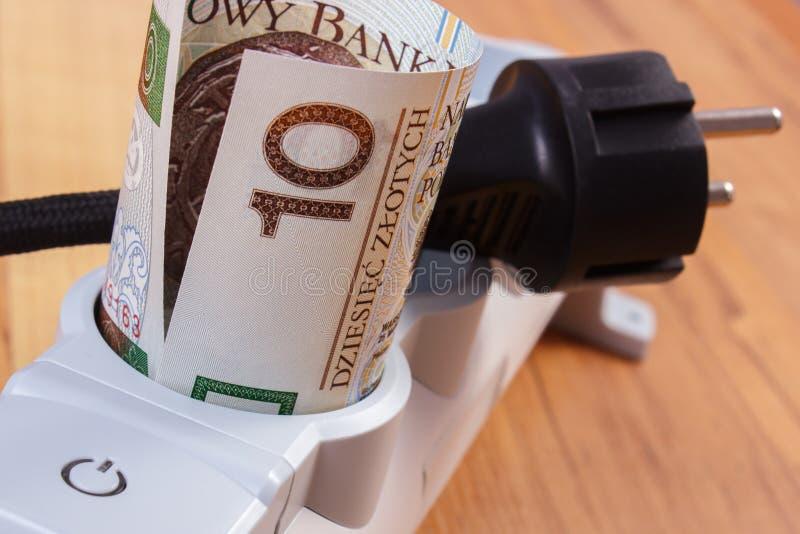 Rolls польских денег валюты в прокладке электропитания и disconnected штепсельной вилке, стоимостях энергии стоковое фото rf