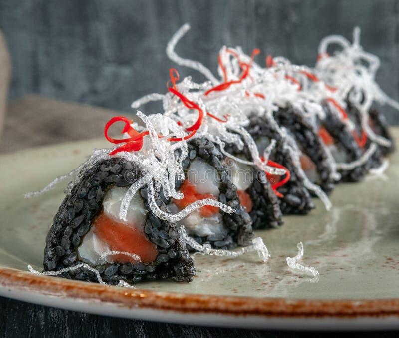Rolls с черным рисом С семгами, тунец, креветка тигра, свежие зеленые луки, в оболочке в хрустящем огурце, украшенном с семгами c стоковые изображения