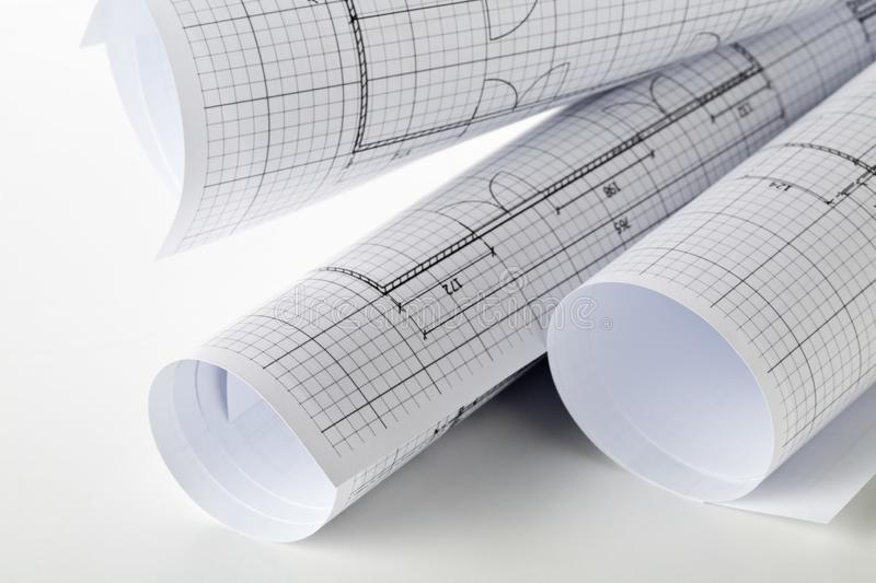Rolls of architectural blueprint house building plans on white table. Background royalty free stock photo