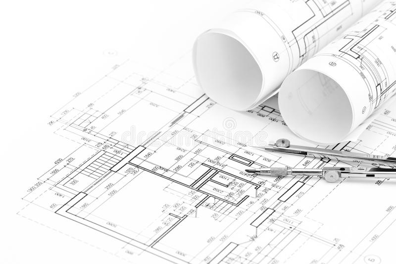 Rolls of architectural blueprints and floor plan with drawing compass stock photos