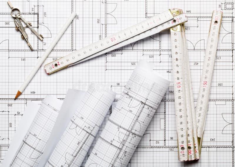 Rolls av arkitektoniska plan för ritninghusbyggnad på ritningbakgrund lägger framlänges med tumstock, blyertspennan och passare royaltyfri foto