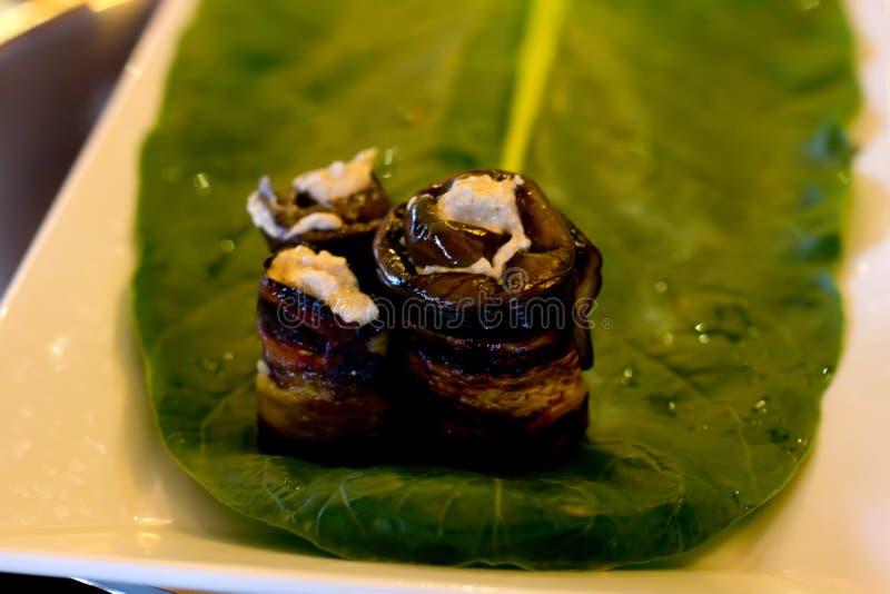 Rolls av aubergine med en fyllning av valnötter som läggas ut på ett ark royaltyfria bilder