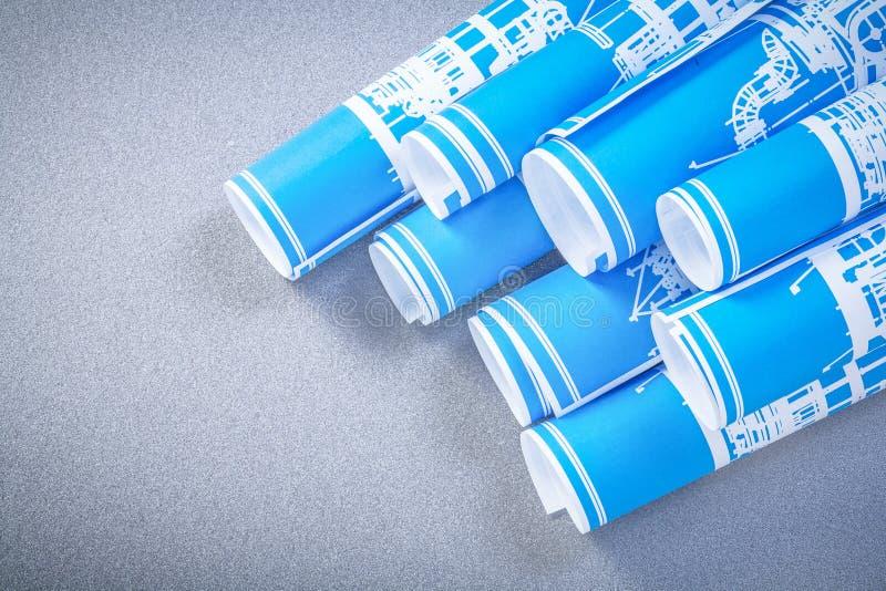 Rolls av blåa konstruktionsplan på grått bakgrundsunderhåll arkivfoton