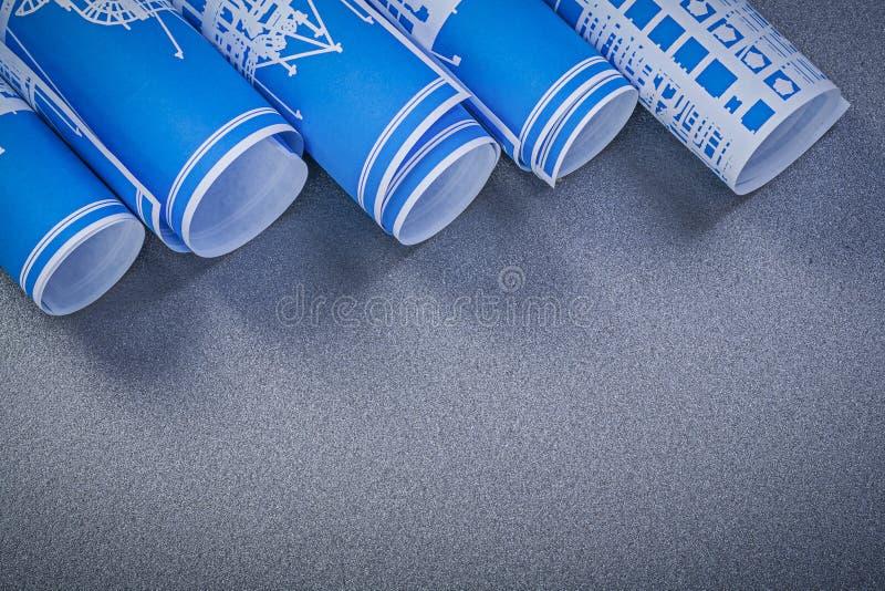 Rolls av blåa teknikteckningar på grå bakgrundsconstructi arkivbild