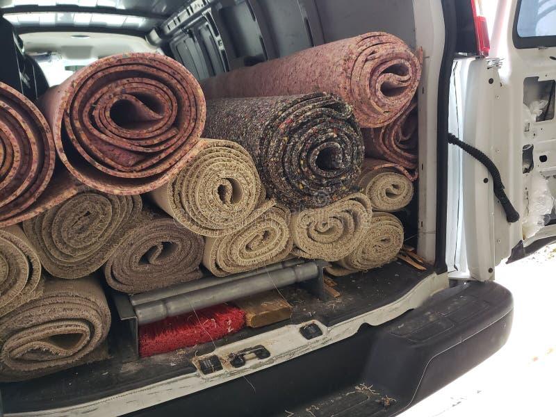 Rolls av gammal matta och att vaddera i lastbilen för installation arkivfoton