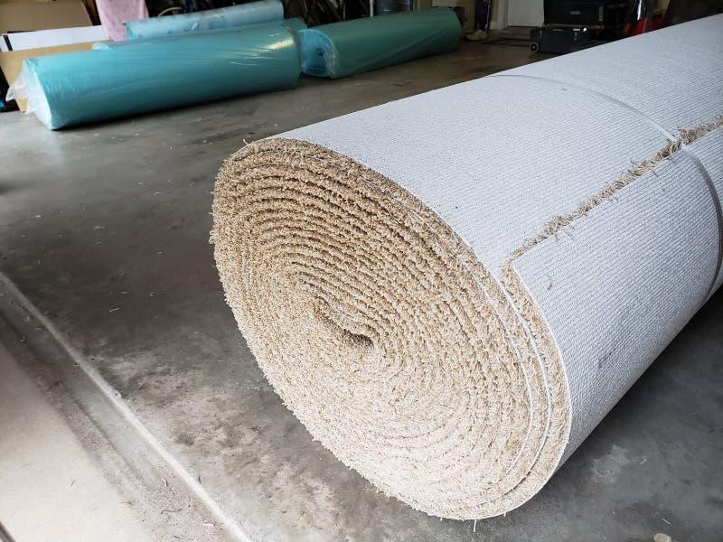 Rolls av ny matta i garaget av huset för att byta ut royaltyfria bilder