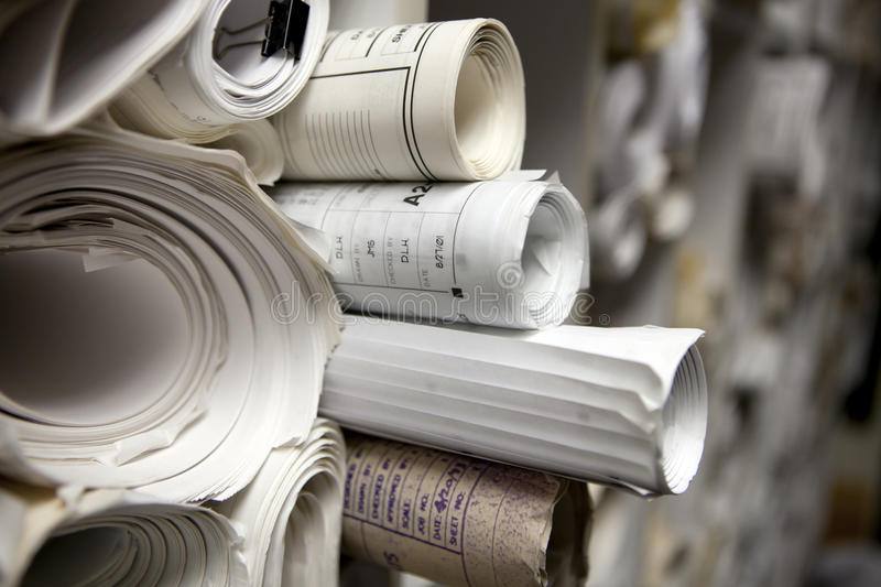 Rolls of Blueprints. Rolled up paper blueprints stacked together stock image
