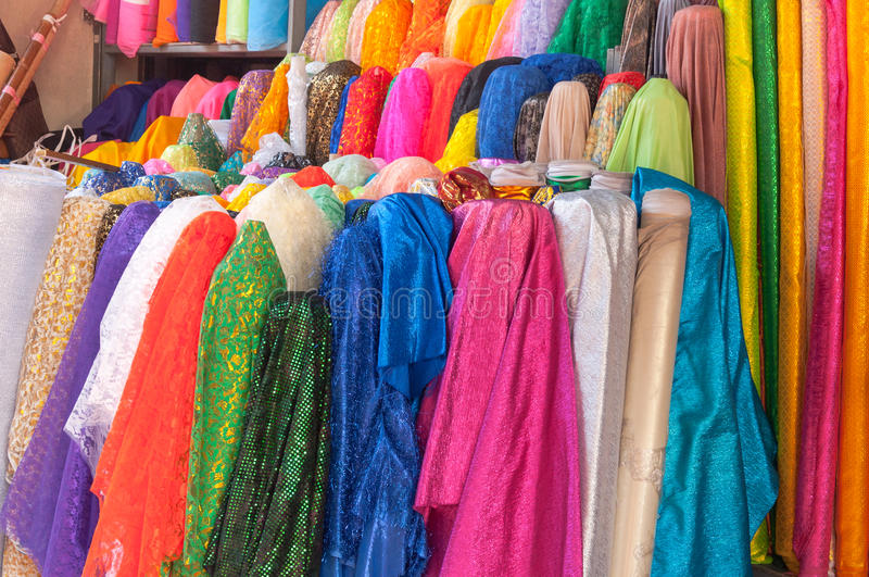 A Rolls of brightly coloured fabrics and cloths stock image