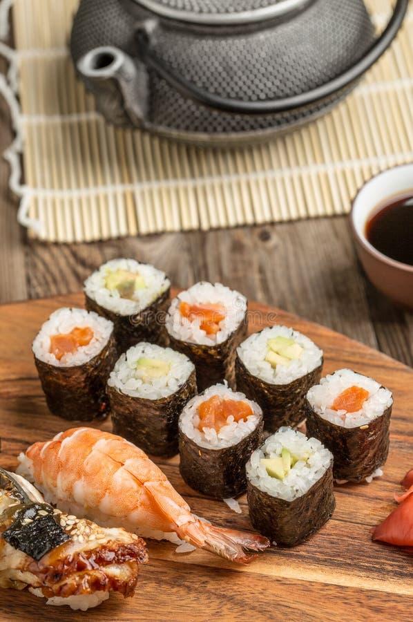 Rolls con el aguacate y el atún, sushi clasificado en la placa de madera fotografía de archivo