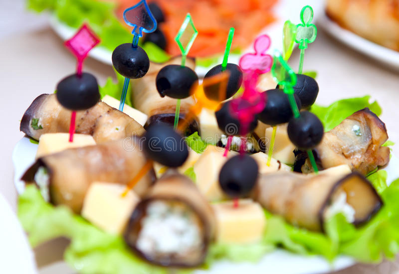 Rolls con el queso, ajo rellenó aceitunas en una tabla festiva imágenes de archivo libres de regalías
