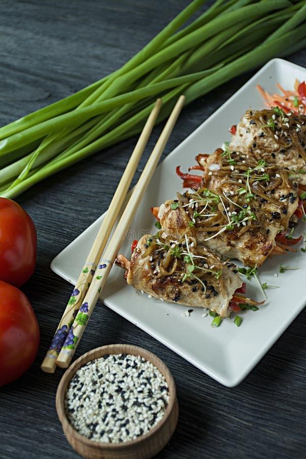 Rolls con il petto di pollo fresco con i verdi, fette della carota, peperoni dolci su un tagliere scuro Il concetto di casalingo  immagine stock