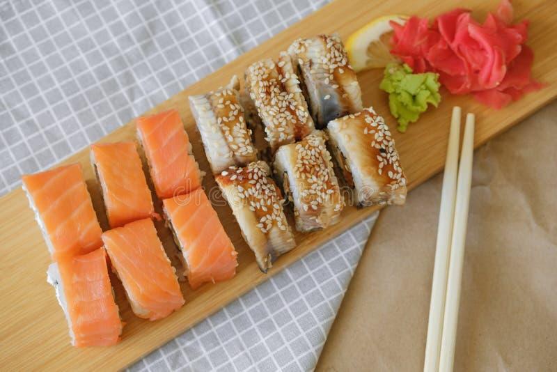 Rolls con il salmone e rotoli con la bugia dell'anguilla su una plancia di legno immagini stock libere da diritti