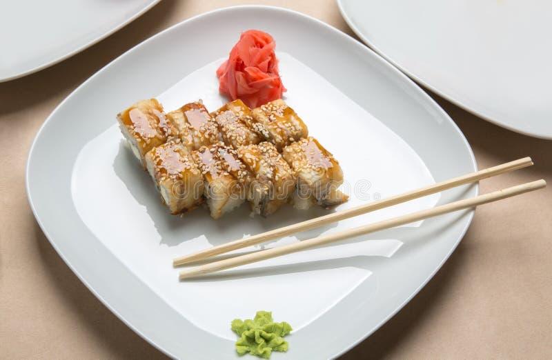 Rolls con l'anguilla e lo zenzero su un piatto bianco immagine stock