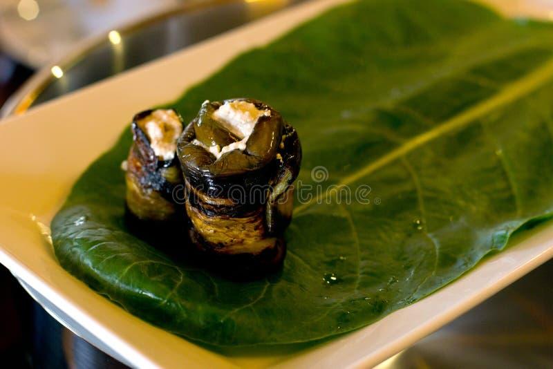 Rolls d'aubergine avec un remplissage des noix, présenté sur une feuille image libre de droits