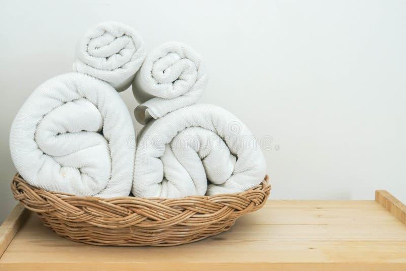 Rolls da toalha branca do algodão na cesta no quarto para o banho fotografia de stock royalty free
