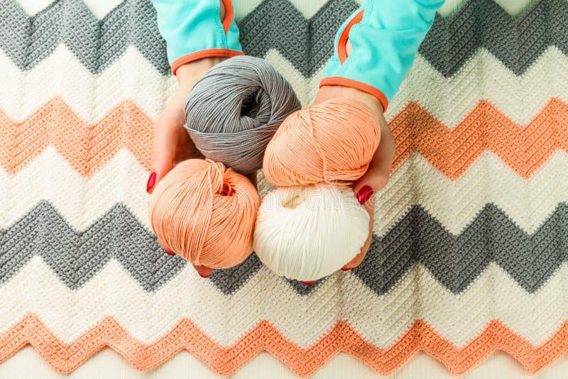 Rolls de fil à tricoter mou, tricotant, mains femelles images stock