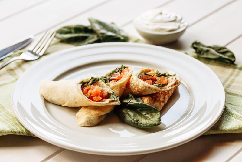 Rolls dei pancake sottili con il salmone affumicato, foglie del formaggio cremoso del rafano e degli spinaci Vista laterale con l fotografia stock libera da diritti