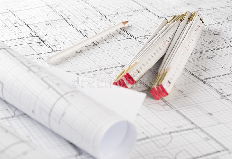 Rolls dei piani architettonici della costruzione di casa del modello con il righello di piegatura e della matita sul fondo del mo fotografia stock