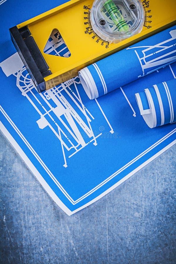 Rolls des dessins industriels bleus nivellent sur le fond métallique image stock