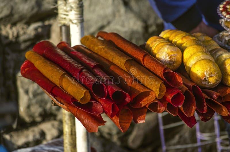 Rolls des pastilles aigres de différentes catégories des prunes sèches et des pêches glacées avec remplir des noix coupées images libres de droits