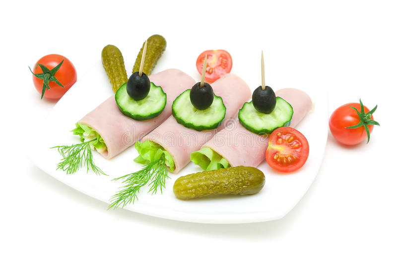 Rolls des Schinkens mit Gemüse auf der Platte auf weißem Hintergrund lizenzfreie stockfotos
