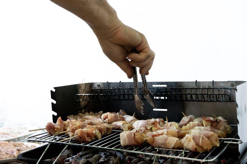 Rolls des Speck- und Hühnerkebabs mit hölzerner Aufsteckspindel in einem Grill mit Holzkohle und Feuer Fleisch im Stock und Koche lizenzfreie stockfotos