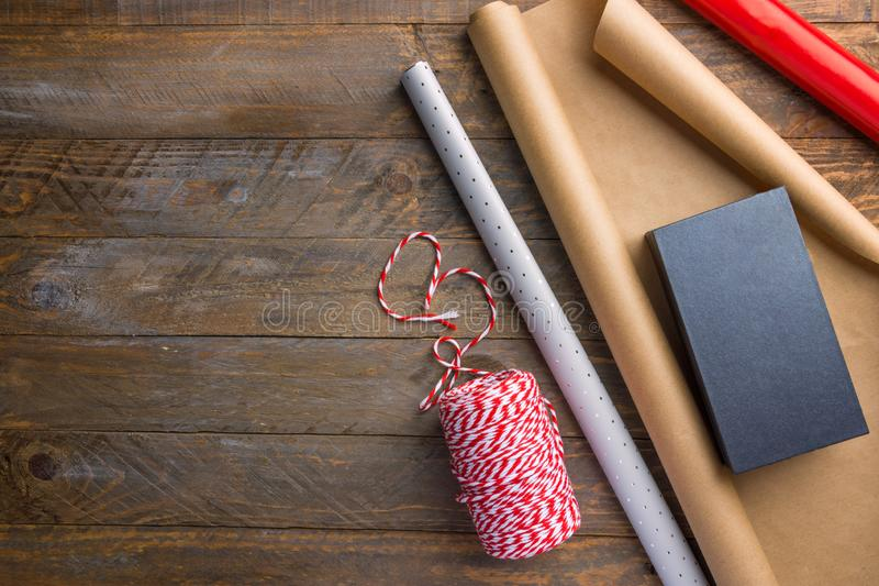 Rolls of different brown Kraft red silver wrapping paper striped ribbon gift box on wood table. Christmas New Year holiday present stock image