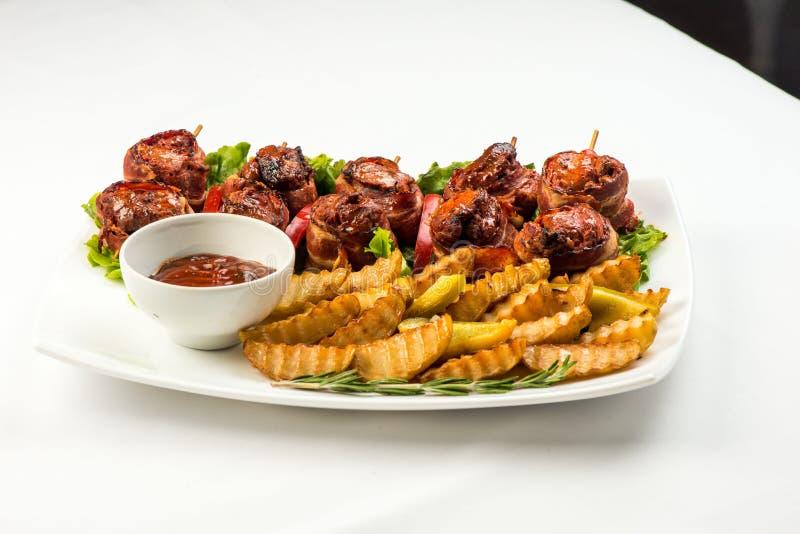 Rolls do bacon e da carne fritada com batatas fritas e molho vermelho na placa branca no fundo branco fotografia de stock royalty free