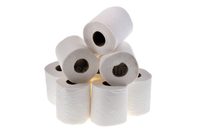 Rolls do papel higiênico empilhado no fundo branco imagens de stock