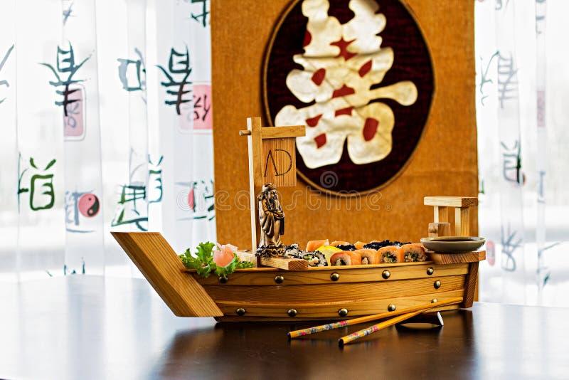 Rolls e sushi in piatti insoliti sulla tavola in ristorante asiatico immagine stock