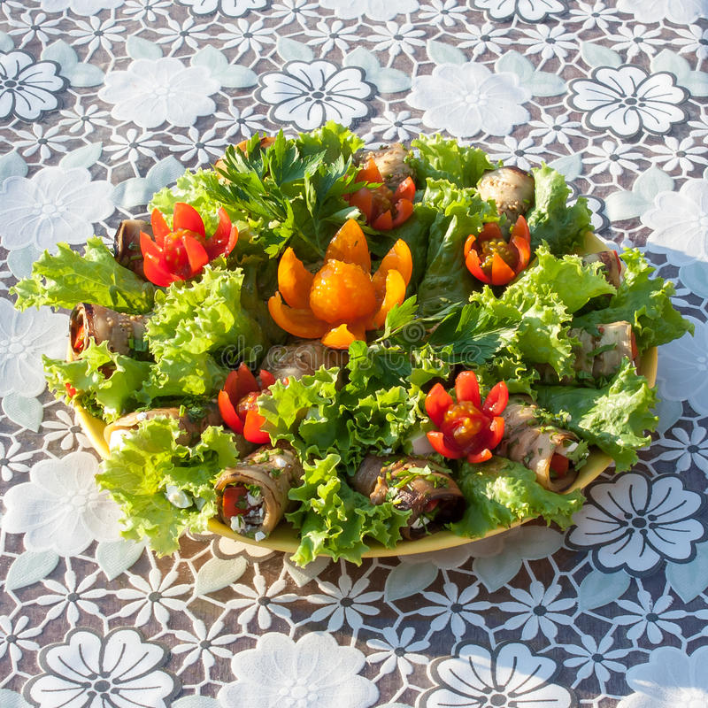 Rolls from eggplant and lettuce leaves decorated with flowers cut from cherry tomatoes on a white tablecloth top view stock photography