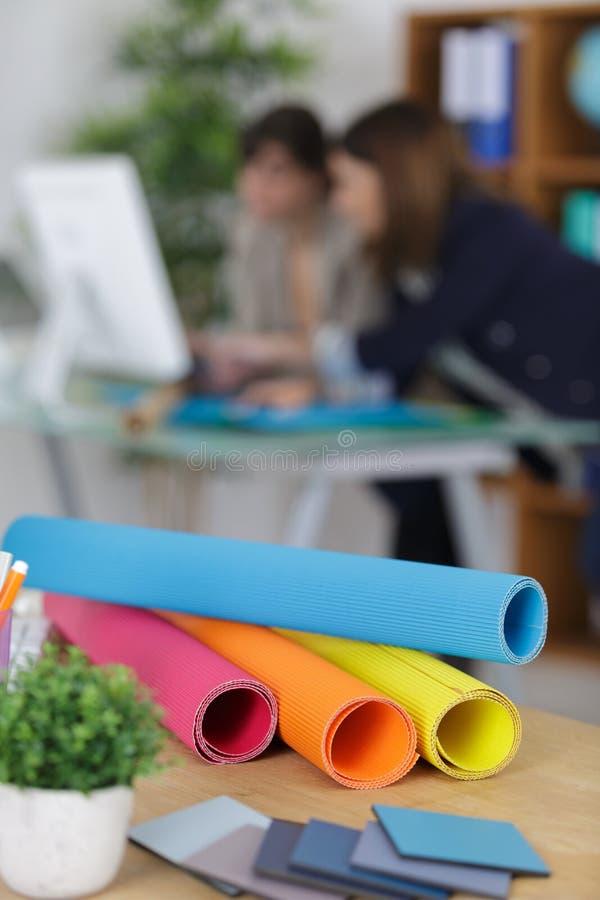Rolls färgade papper i upptaget kontor för förgrund royaltyfri fotografi