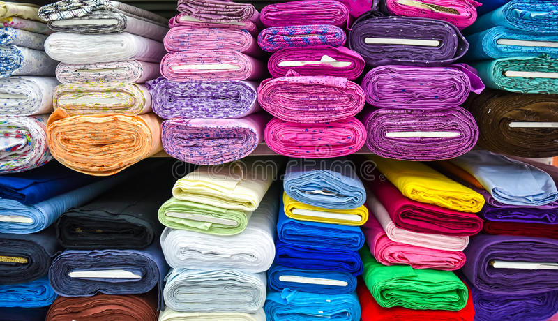 Rolls of fabric and textiles in a factpory shop. Rolls of fabric and textiles in a factory shop. Multi different colors and patterns on the market stock images