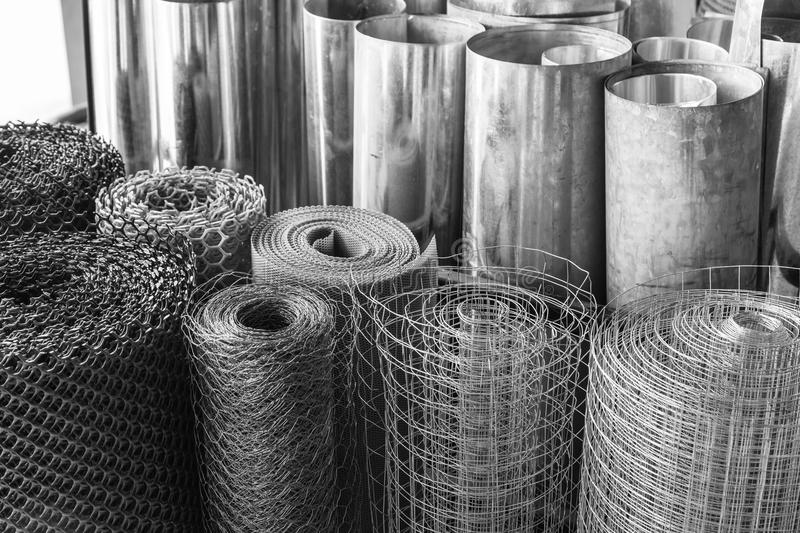 Rolls of galvanized metal sheets, steel chicken wire mesh, and p royalty free stock photo