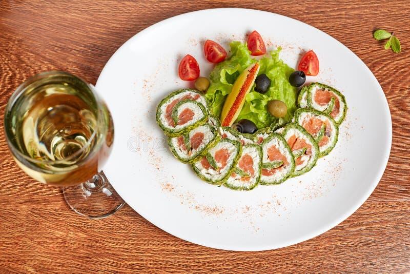 Rolls mit Lachs-, Frischkäse in einem Wasabipfannkuchen, Lüge auf einer Platte mit einer Scheibe der Zitrone, Oliven, Kirschtomat stockfotografie