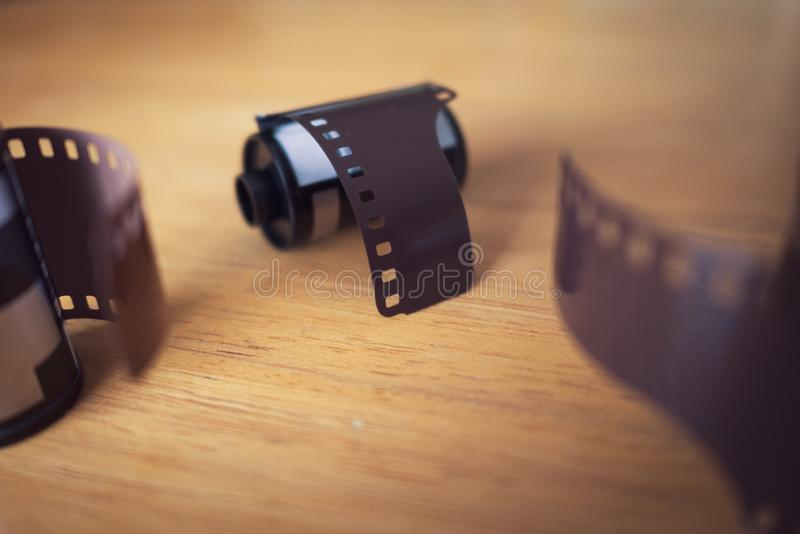 Rolls of 35 mm film for cameras on wooden table.  royalty free stock photography