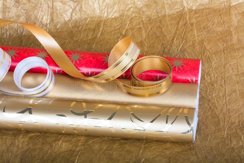 Rolls of multicolored wrapping paper with streamer for gifts. On gold abstract background royalty free stock image