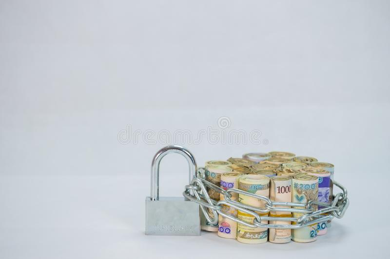Rolls of Naira Cash local currencies with chain and padlock. Rolls and Bundles of Naira Cash local currencies with chain and padlock depicting  online security stock photos