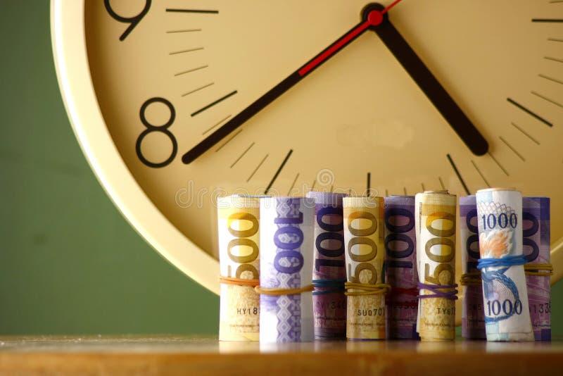 Rolls of paper money an analog clock. Rolls of paper money and an analog clock stock photos