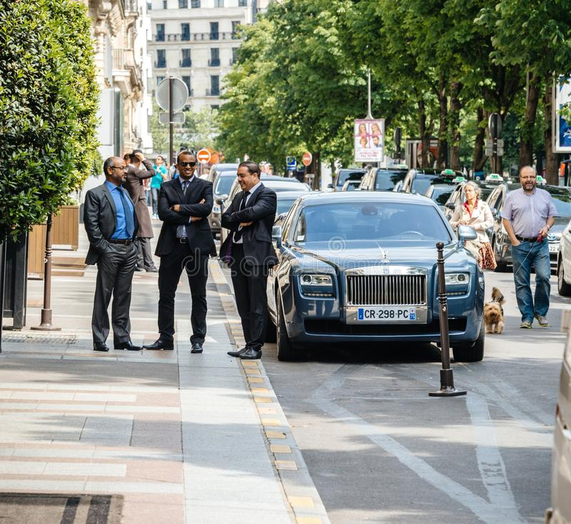 Rolls-Royce parked near George V hotel. PARIS, FRANCE - MAY 21, 2016: Drivers and security personnel talking near elegant Rolls-Royce car parked in front of stock photo