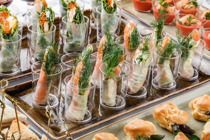 Rolls of salmon fish with cream cheese, avocado and greens on banquet table. Gourmet food close up, snack, antipasti. Seafood platter royalty free stock image