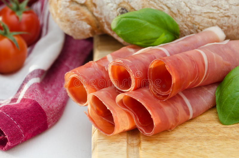 Rolls of serrano ham. Garnished with basil and bread stock photos