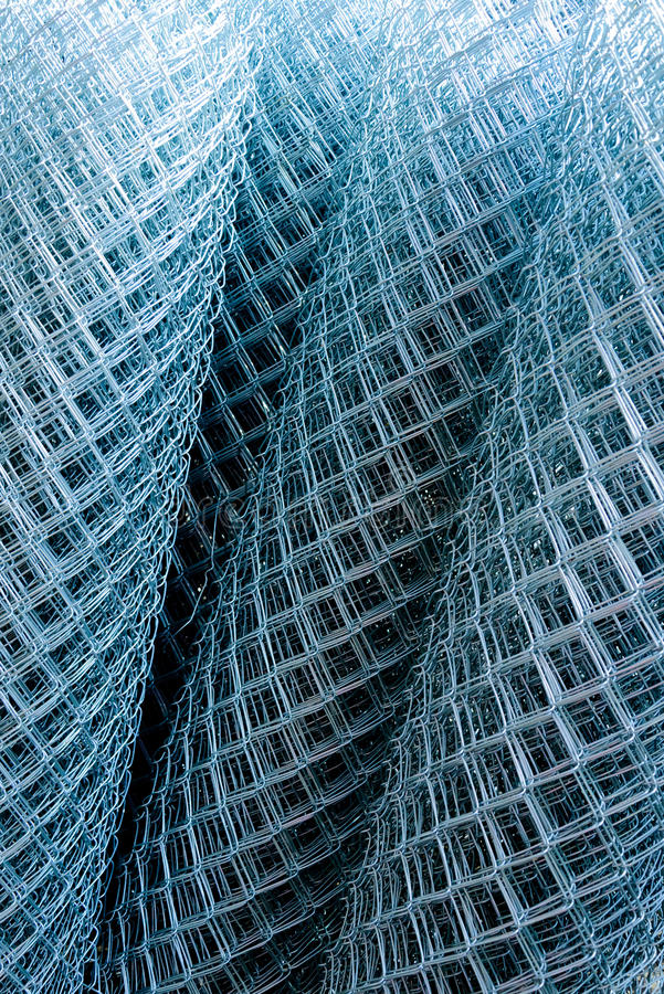 Rolls of shiny new chain link fence. Rolled supplies of shiny new chain link fence royalty free stock images