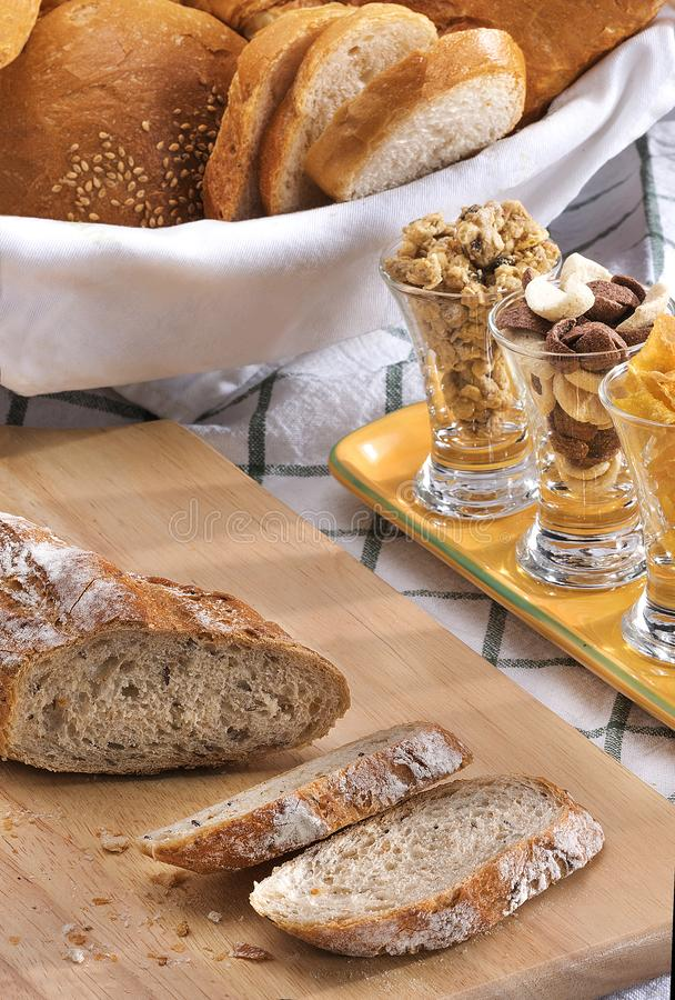 Rolls, sliced breads, cereal at breakfast service table. Breads cornflakes and cereals offered in style breakfast at breakfast service royalty free stock photos