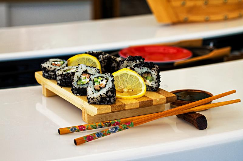 Rolls and sushi in traditional dishes on the table in asian restaurant royalty free stock photography